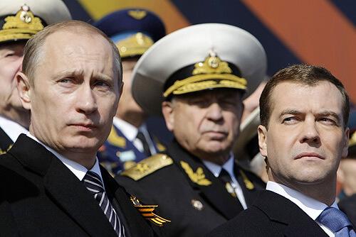 Russlands Präsident Wladimir Putin und Ministerpräsident Dmitri Medwedjew vor Generälen